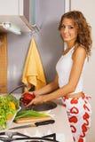 Vegetais de lavagem da mulher bonita nova fotos de stock