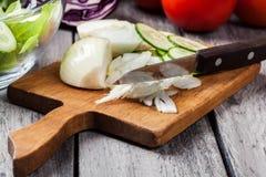 Vegetais desbastados: cebola e pepino na placa de corte Imagens de Stock