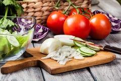 Vegetais desbastados: cebola e pepino na placa de corte Foto de Stock Royalty Free