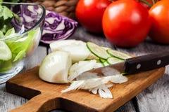 Vegetais desbastados: cebola e pepino na placa de corte Fotografia de Stock