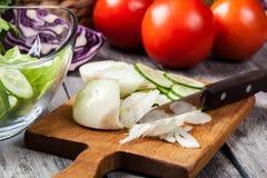 Vegetais desbastados: cebola e pepino na placa de corte Foto de Stock