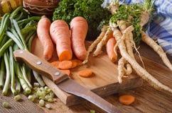 Vegetais desbastados: cenouras, salsa e cebola na placa de corte Fotos de Stock Royalty Free