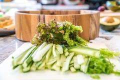 Vegetais desbastados e cortados na placa de corte pronta para uma refeição do sushi do vegetariano na frente de uma bacia de made Fotos de Stock Royalty Free