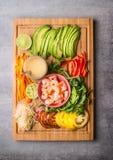 Vegetais desbastados: o abacate, os tomates, a paprika, o cal e os brotos com camarão e amendoim mergulham na placa de corte de m Fotos de Stock Royalty Free