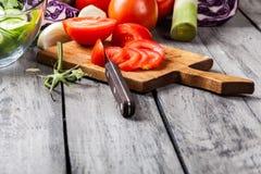 Vegetais desbastados: tomates na placa de corte Imagens de Stock Royalty Free