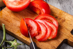 Vegetais desbastados: tomates na placa de corte Imagens de Stock