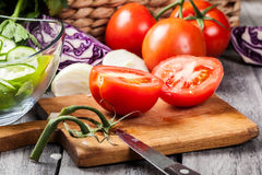 Vegetais desbastados: tomates na placa de corte Fotos de Stock Royalty Free