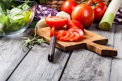Vegetais desbastados: tomates na placa de corte Imagem de Stock Royalty Free