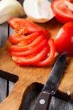 Vegetais desbastados: tomates na placa de corte Fotos de Stock