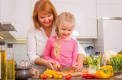 Vegetais do corte da mãe e da filha na cozinha imagem de stock royalty free