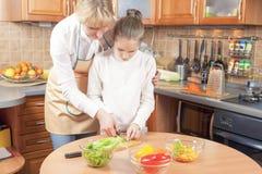 Vegetais do corte da mãe e da filha para a salada foto de stock royalty free