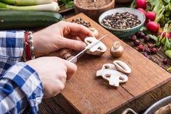 Vegetais do corte da mão As mãos das mulheres estão cortando cogumelos na placa de madeira perto dos vegetais Imagem de Stock Royalty Free