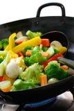 Vegetais do cozinheiro em um wok chinês Foto de Stock Royalty Free