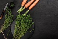 Vegetais do vegetariano do verão, cenouras e tomilho crus saudáveis da erva no fundo de pedra escuro fotos de stock