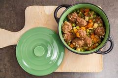 Vegetais e carne cozinhada em uma bacia profunda preta em um fundo cinzento O conceito do alimento natural e saudável imagem de stock