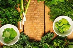 Vegetais e especiarias verdes em umas bacias em uma tabela de madeira Imagens de Stock