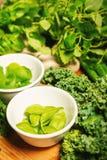 Vegetais e especiarias verdes em umas bacias em uma tabela de madeira Foto de Stock