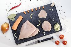 Vegetais e galinha cortados em uma placa de corte escura imagem de stock royalty free
