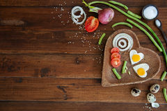 Vegetais e uma placa com os ovos fritos no tiro ascendente do fim de madeira das despesas gerais do fundo Imagem de Stock Royalty Free