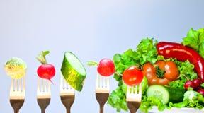 Vegetais em forquilhas em um fundo de legumes frescos Fotos de Stock
