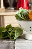 Vegetais em um escorredor e na mesa de cozinha Imagem de Stock Royalty Free