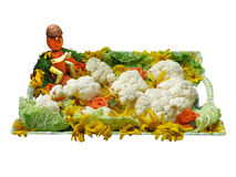 Vegetais em uma bandeja com a estatueta engraçada isolada sobre o branco Fotografia de Stock