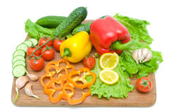 Vegetais em uma placa de corte em um close-up branco do fundo. Fotografia de Stock