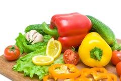 Vegetais em uma placa de corte em um fundo branco Imagens de Stock Royalty Free