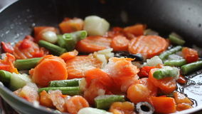 Vegetais fritados em uma frigideira filme
