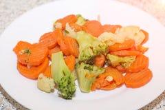 Vegetais fritados em uma placa branca Cenouras, brócolis e caulifl Foto de Stock