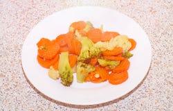 Vegetais fritados em uma placa branca Cenouras, brócolis e caulifl Imagens de Stock Royalty Free