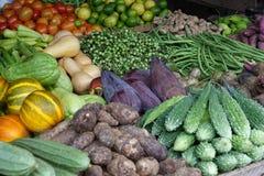 Vegetais maduros empilhados no contador em um mercado local das frutas e legumes fotografia de stock