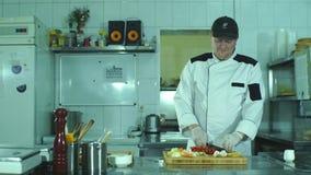 Vegetais na placa de corte e no detalhe das mãos do cozinheiro chefe, cozinha do restaurante no fundo video estoque