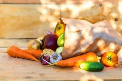 Vegetais no saco de papel no fundo de madeira Foto de Stock Royalty Free