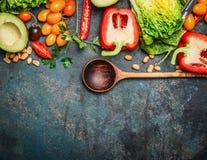 Vegetais orgânicos coloridos com colher de madeira, ingredientes para a salada ou enchimento no fundo de madeira rústico, vista s