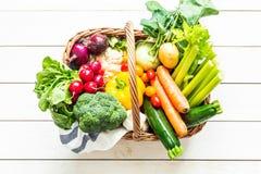 Vegetais orgânicos coloridos da mola na cesta de vime na madeira Imagem de Stock Royalty Free
