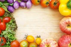 Vegetais orgânicos frescos coloridos que compõem um quadro em uma placa de desbastamento de madeira Imagem de Stock Royalty Free