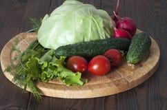 Vegetais para a salada em uma placa de corte Imagens de Stock