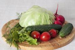 Vegetais para a salada em uma placa de corte Fotos de Stock