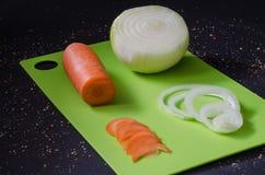 Vegetais saudáveis na placa de corte verde e no backgroud do preto escuro Fotografia de Stock Royalty Free