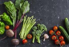 Vegetais sazonais frescos - beterrabas, aspargo, brócolis, tomates, pimentas, pepinos em um fundo escuro Conceito saudável do ali Imagem de Stock Royalty Free