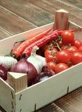 Vegetais sortidos em uma caixa de madeira em um fundo de madeira Imagem de Stock Royalty Free