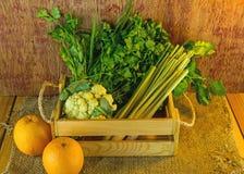 Vegetais sortidos na caixa de madeira em de madeira rústico escuro e no saco s Foto de Stock Royalty Free