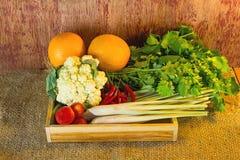 Vegetais sortidos na caixa de madeira em de madeira rústico escuro e no saco s Imagens de Stock Royalty Free