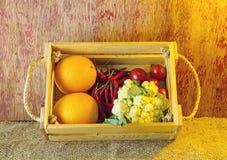 Vegetais sortidos na caixa de madeira em de madeira rústico escuro e no saco s Fotos de Stock Royalty Free