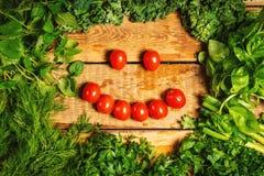 Vegetais verdes e um sorriso com tomates em uma tabela de madeira Imagem de Stock Royalty Free