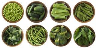 Vegetais verdes isolados em um fundo branco Brocoli, ervilhas verdes, pepinos e folhas salsa, aipo, espinafre na bacia de madeira Fotos de Stock