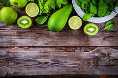 Vegetais verdes: quivi, espinafre, abacate, cal, aipo em um fundo de madeira rústico Vista de acima Imagem de Stock