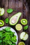 Vegetais verdes: quivi, espinafre, abacate, maçã, cal em um fundo de madeira rústico Vista de acima Imagens de Stock Royalty Free