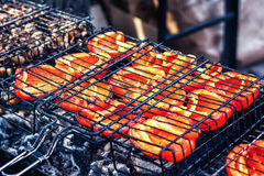 Vegetais vermelhos suculentos frescos belamente roasted das pimentas de sino na grade sobre o baixo calor para preparar-se Fotografia de Stock Royalty Free
